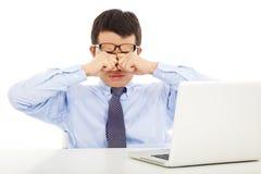 El hombre de negocios joven cansado que frota el suyo observa con el ordenador portátil Fotos de archivo