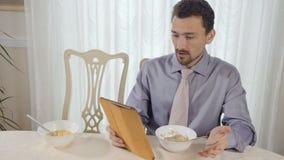 El hombre de negocios joven come muesli usando la tableta