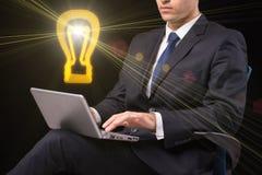 El hombre de negocios joven con concepto de la idea del ordenador portátil y de la lámpara imágenes de archivo libres de regalías