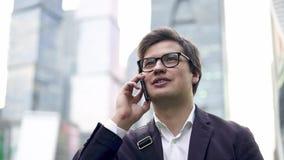 El hombre de negocios joven confiado que habla en su teléfono en la ciudad de Moscú, inclina abajo