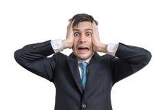 El hombre de negocios joven divertido subrayado está llevando a cabo su cabeza Aislado en el fondo blanco fotos de archivo