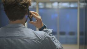 El hombre de negocios joven, elegante entra en su oficina y charla sobre un teléfono móvil almacen de metraje de vídeo