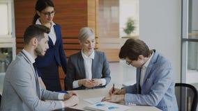 El hombre de negocios joven en contrato de firma del traje y sacude las manos con su colega mientras que abogado corporativo que