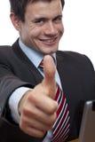 El hombre de negocios joven en el escritorio muestra el pulgar para arriba Imagen de archivo