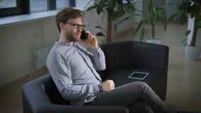 El hombre de negocios joven en el sofá está hablando con su socio almacen de metraje de vídeo