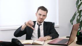 El hombre de negocios joven en el traje que se sienta en oficina y que muestra manosea con los dedos encima de fps de la muestra  metrajes