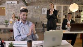 El hombre de negocios joven es feliz debido al logro en la oficina, colegas lo está felicitando, trabajando concepto metrajes