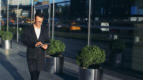El hombre de negocios joven está caminando a lo largo de la calle de la ciudad con una tableta en sus manos Tiro épico rojo del d