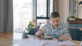 El hombre de negocios joven está en el almuerzo de negocios, usando el teléfono que se sienta en café metrajes