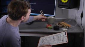 El hombre de negocios joven está gozando del sushi en su escritorio durante tiempo del almuerzo Freelancer que tiene rotura para  metrajes