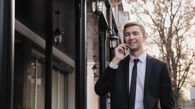 El hombre de negocios joven está hablando en el teléfono elegante almacen de video
