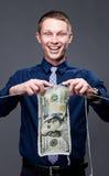 El hombre de negocios joven está haciendo punto un billete de banco del dólar Fotos de archivo libres de regalías