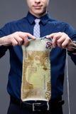 El hombre de negocios joven está haciendo punto un billete de banco euro Foto de archivo