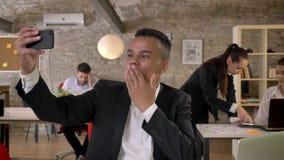 El hombre de negocios joven está haciendo el selfie en smartphone en la oficina, soplando un beso, engaña alrededor, sus colegas  almacen de metraje de vídeo