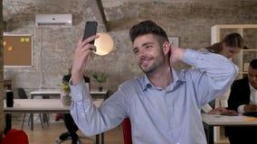 El hombre de negocios joven está haciendo el selfie en smartphone en oficina, sus colegas es establecimiento de una red con las t almacen de video