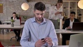 El hombre de negocios joven está mecanografiando en smartphone en oficina, sus colegas está tomando las fotos de documentos, trab metrajes
