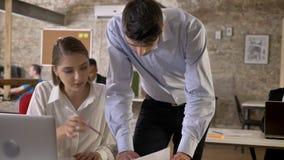 El hombre de negocios joven está mostrando los papeles a su colega en la oficina, establecimiento de una red con tecnologías, con metrajes