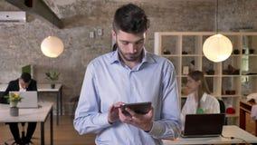 El hombre de negocios joven está practicando surf Internet en la tableta en la oficina, mirando en la cámara, sus colegas es esta almacen de metraje de vídeo