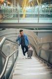 El hombre de negocios joven está subiendo las escaleras en el aeropuerto que habla por t foto de archivo libre de regalías