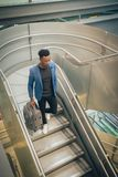 El hombre de negocios joven está subiendo las escaleras en el aeropuerto que habla por t foto de archivo