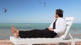 El hombre de negocios joven est? trabajando en la playa El profesional masculino se est? sentando en ocioso c?modo almacen de metraje de vídeo