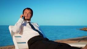 El hombre de negocios joven est? trabajando en la playa El profesional masculino se est? sentando en ocioso c?modo almacen de video