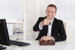 El hombre de negocios joven feliz que se sienta en su oficina da el consejo para el Cu foto de archivo