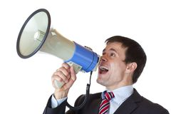 El hombre de negocios joven grita en alta voz en el megáfono Imagenes de archivo