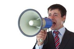 El hombre de negocios joven grita en alta voz en el megáfono Foto de archivo