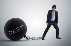 El hombre de negocios joven ha encadenado la bola de metal grande a su pierna con la deuda escrita imagenes de archivo
