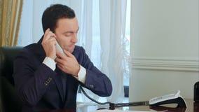 El hombre de negocios joven hace preocupante y enojado después teniendo una llamada de teléfono y pone el teléfono abajo metrajes