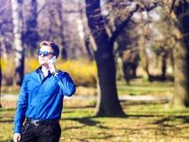 El hombre de negocios joven hermoso que habla en hes llama por teléfono en el bosque Imagen de archivo