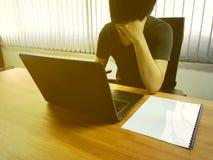 El hombre de negocios joven lleva a cabo la cabeza con la mano durante el trabajo en la oficina fotos de archivo
