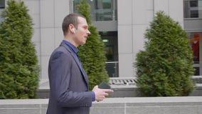 El hombre de negocios joven que camina abajo de la calle con los auriculares inal?mbricos y lleva agresivamente una discusi?n sob almacen de video