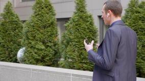 El hombre de negocios joven que camina abajo de la calle con los auriculares inal?mbricos y lleva agresivamente una discusi?n sob