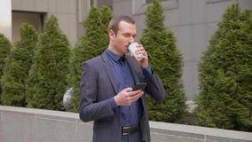 El hombre de negocios joven que camina abajo de la calle con un vidrio de caf? en su mano escribe un mensaje en el tel?fono
