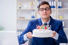 El hombre de negocios joven que celebra cumpleaños solamente en oficina Foto de archivo libre de regalías