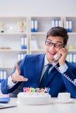 El hombre de negocios joven que celebra cumpleaños solamente en oficina Imagen de archivo libre de regalías