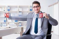 El hombre de negocios joven que ejercita con el ampliador elástico en oficina fotos de archivo libres de regalías