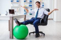 El hombre de negocios joven que hace los deportes que estiran en el lugar de trabajo imagen de archivo libre de regalías