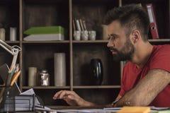 El hombre de negocios joven que se sienta detrás del escritorio y envía correos electrónicos usando el ordenador portátil imagenes de archivo
