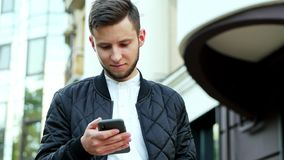 El hombre de negocios joven que sostiene el teléfono móvil moderno, hombre está mecanografiando el SMS, charlando almacen de metraje de vídeo