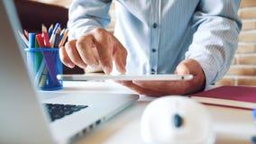 El hombre de negocios joven que trabaja con la tableta y y lee el correo electrónico en su oficina en el lugar de trabajo