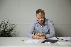 El hombre de negocios joven ríe y disfruta en las noticias recibidas por el teléfono móvil que se sienta en el escritorio en el l Fotos de archivo