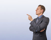 El hombre de negocios joven señala con su finger en el lado izquierdo - con el copyspace Escéptico, crítico o el analizar imagen de archivo