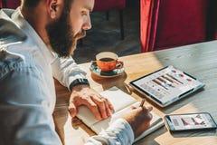 El hombre de negocios joven se está sentando en la tabla y está haciendo notas en cuaderno En la tabla es la tableta, smartphone  Fotos de archivo libres de regalías
