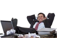 El hombre de negocios joven se relaja con los pies en el escritorio Fotos de archivo libres de regalías