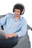 El hombre de negocios joven se relaja con música y la computadora portátil Imagenes de archivo