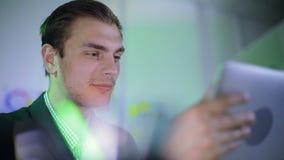 El hombre de negocios joven sonríe ampliamente y lee algo en la tableta almacen de video