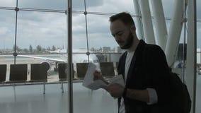 El hombre de negocios joven sostiene el boleto y el pasaporte que se colocan en el edificio del aeropuerto metrajes